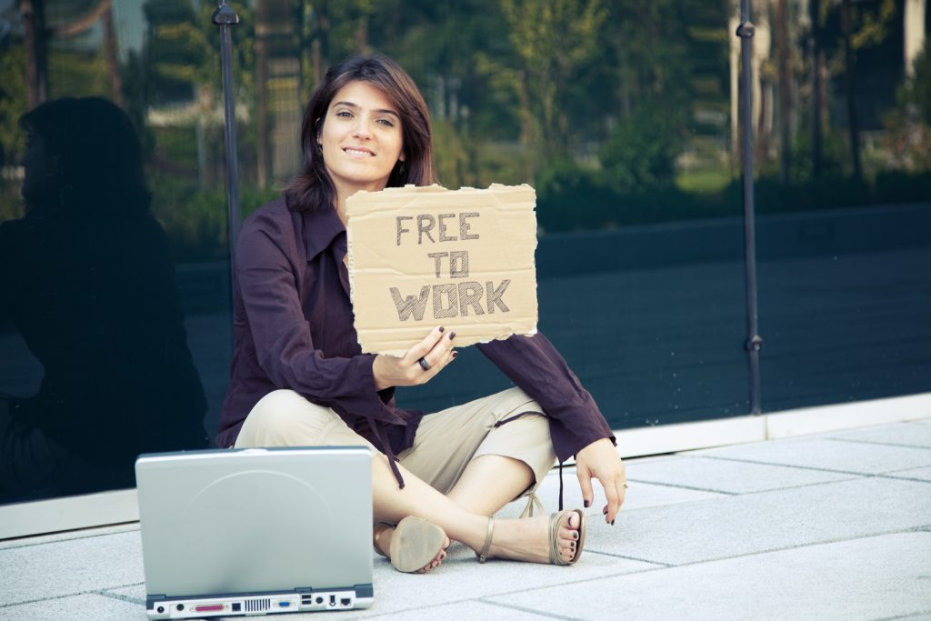 Professional woman sitting on sidewalk holding job search sign